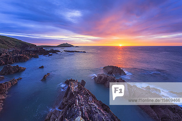 Sun rising over the Irish coastline with jagged rocks in the foreground and a lighthouse on an island in the distance; Ballycotton  County Cork  Ireland