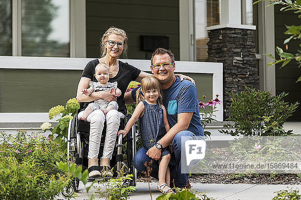A young family posing for a family portrait outdoors in their front yard and the mother is a paraplegic in a wheelchair; Edmonton  Alberta  Canada