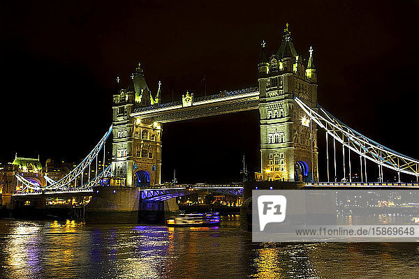 Tower Bridge illuminated at nighttime and reflected in the tranquil water of the River Thames; London  England