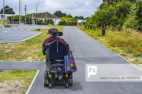 Maori woman with Cerebral Palsy in a wheelchair going down a sidewalk; Wellington  New Zealand