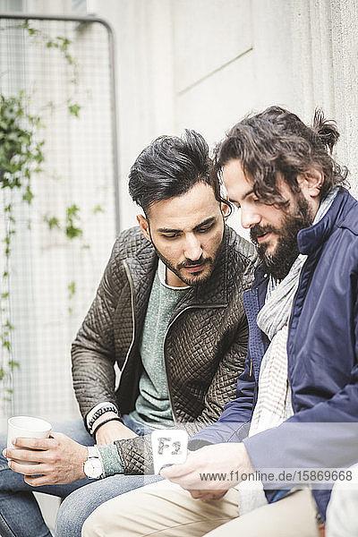 Junger Geschäftsmann zeigt einem männlichen Kollegen sein Handy  während er im Kreativbüro sitzt