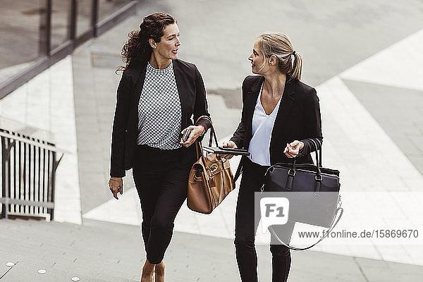 Geschäftsfrau im Gespräch mit einer Kollegin beim Treppensteigen