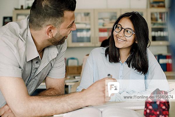 Lächelnder männlicher Lehrer erklärt dem Schüler  während er sich im Klassenzimmer auf den Tisch lehnt