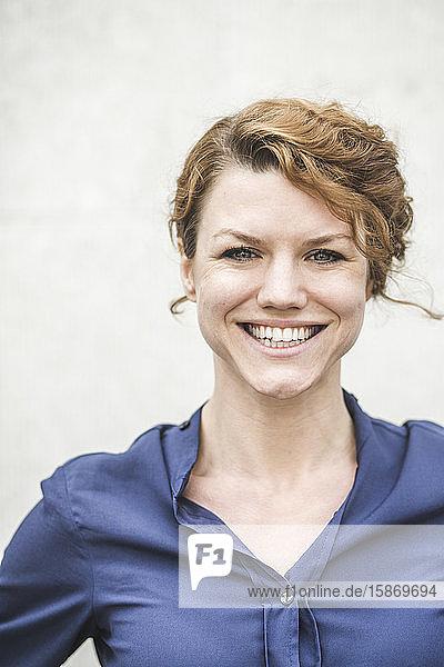 Porträt einer lächelnden Unternehmerin  die an der Wand steht