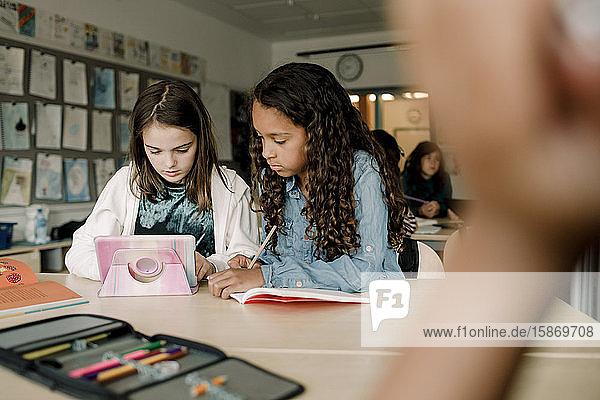 Studentinnen  die Tabletten am Tisch im Klassenzimmer benutzen