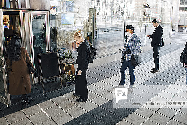 Menschen stehen in der Schlange vor dem Café und halten Abstand