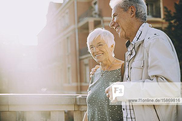 Lächelndes älteres Paar mit umarmtem Arm an einem sonnigen Tag in der Stadt spazieren