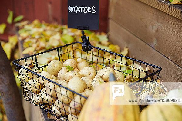 Hochwinkelansicht von rohen Kartoffeln im Korb am Tisch