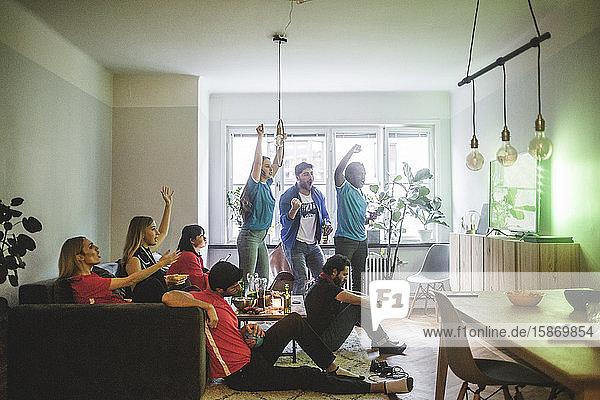 Fröhliche Freunde und Freundinnen sehen sich zu Hause ein Fußballspiel an