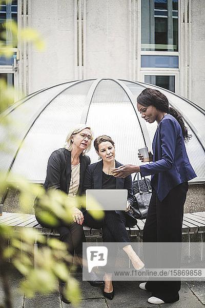 Geschäftsfrau in voller Länge zeigt weiblichen Mitarbeitern im Bürohof ein Smartphone