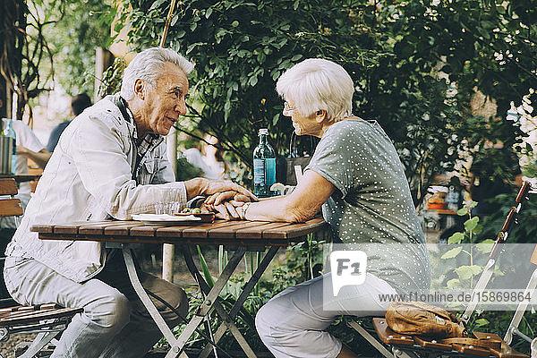 Älteres Ehepaar  das sich im Restaurant in der Stadt an den Händen hält