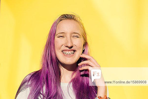 Porträt eines lächelnden Teenager-Mädchens vor gelbem Hintergrund