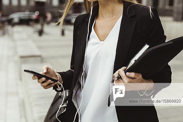 Mittendrin Unternehmerin mit Mobiltelefon auf dem Bürgersteig stehend