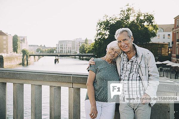 Porträt eines lächelnden älteren Paares  das in der Stadt mit dem Arm gegen das Geländer steht