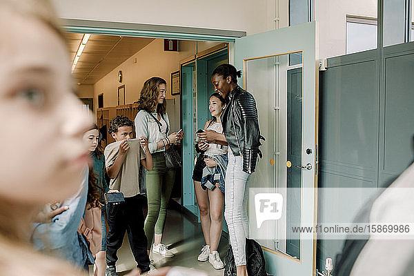 Lächelnde Junior-High-Schüler stehen an der Tür im Schulkorridor