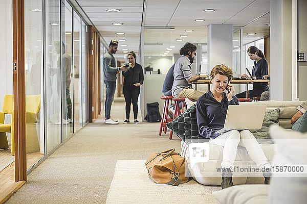 Männliche und weibliche Geschäftsleute  die im Kreativbüro arbeiten