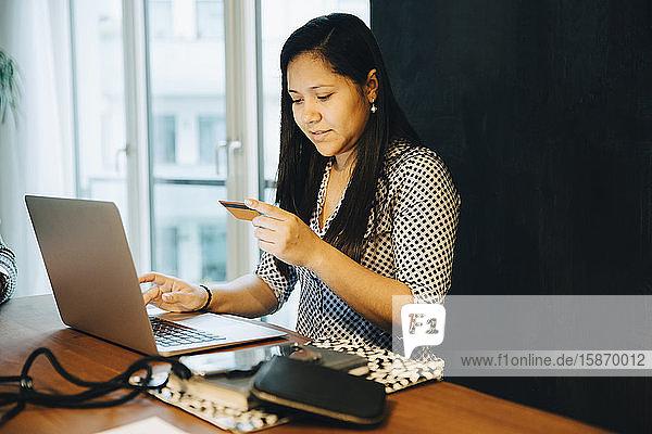 Frau mit Kreditkarte beim Online-Shopping am Laptop  während sie zu Hause sitzt