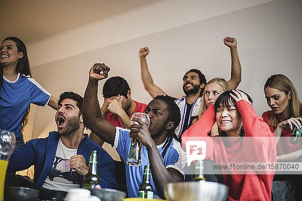 Multiethnische Freunde sehen sich ein Fußballspiel an  während sie zu Hause an der Wand sitzen