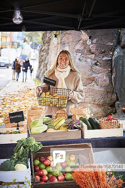 Porträt einer lächelnden Frau  die am Marktstand einen Korb mit frischen Kartoffeln hält