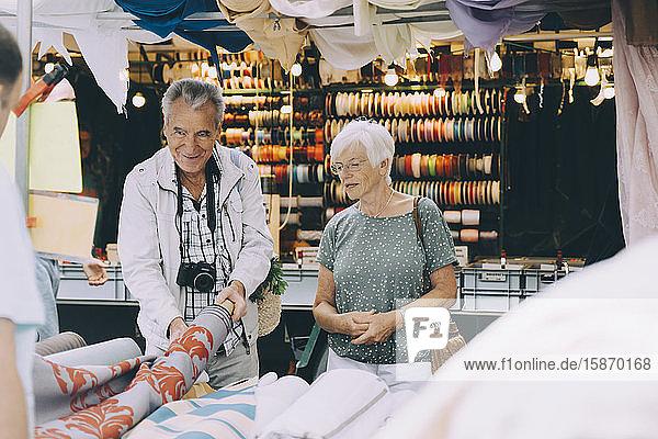 Älterer Mann hält Musterstoff in der Hand  während er mit Frau auf dem Markt in der Stadt einkauft