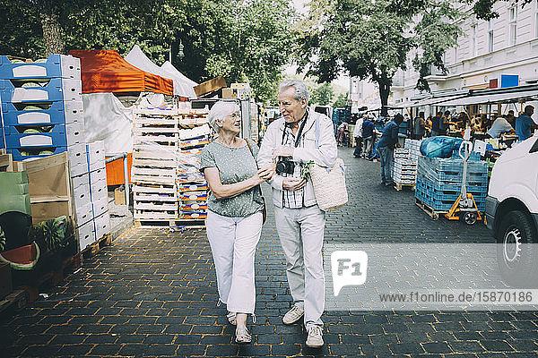 Älteres Ehepaar spricht in voller Länge  während es Arm in Arm auf dem Straßenmarkt geht