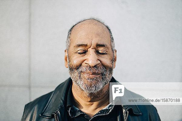 Lächelnder älterer Mann mit geschlossenen Augen an der Wand