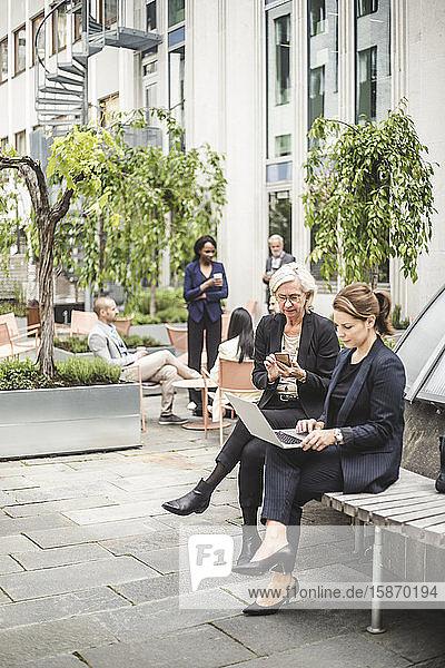 Geschäftsfrauen in voller Länge mit Laptop  während sie mit Kollegen auf der Bank im Hintergrund im Bürohof sitzen