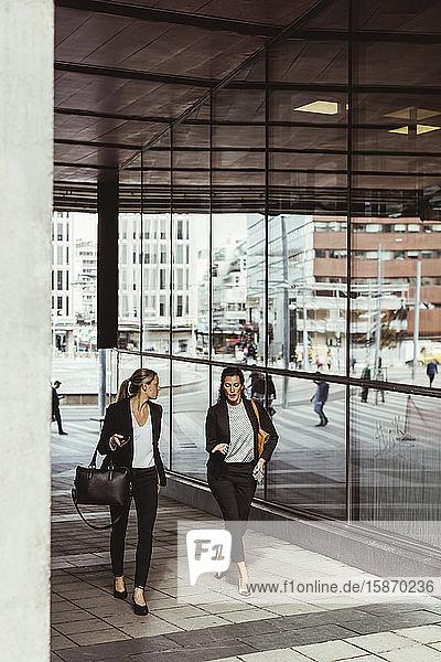 Geschäftsfrauen im Gespräch beim Gehen auf dem Fußweg