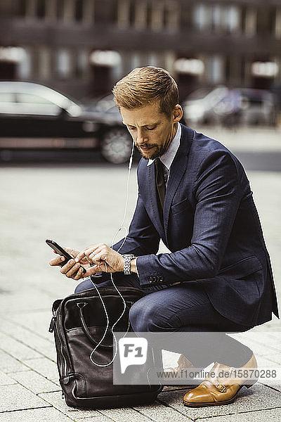 Männlicher Unternehmer schaut auf die Zeit  während er auf der Straße kauert