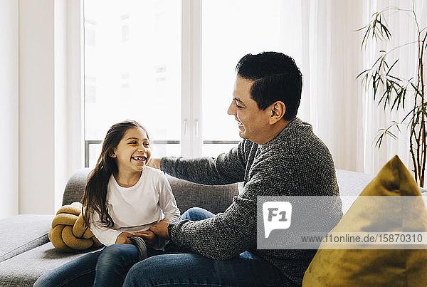 Lächelnder Vater und Tochter sitzen zu Hause auf dem Sofa vor dem Fenster