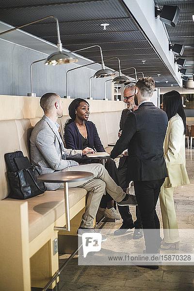 Männliche und weibliche Geschäftskollegen diskutieren während der Kaffeepause im Büro
