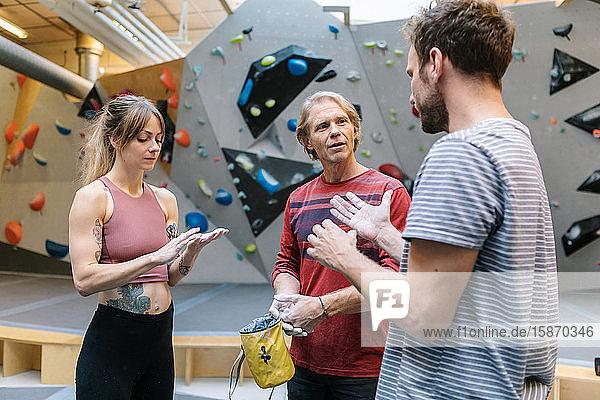 Ausgereifter Trainer  der männliche und weibliche Studenten für das Wandklettern im Fitnessstudio ausbildet