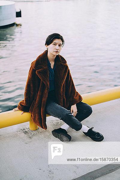 Junge Frau in voller Länge am See sitzend