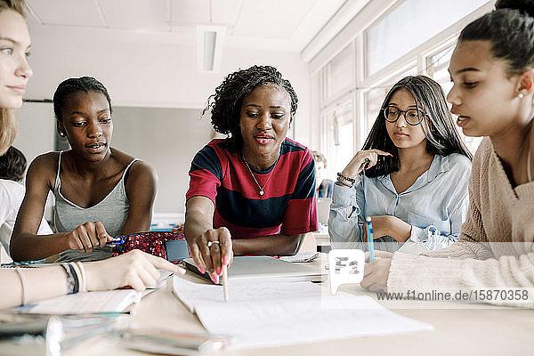 Lehrerin erklärt  während Studentinnen im Klassenzimmer am Tisch lernen