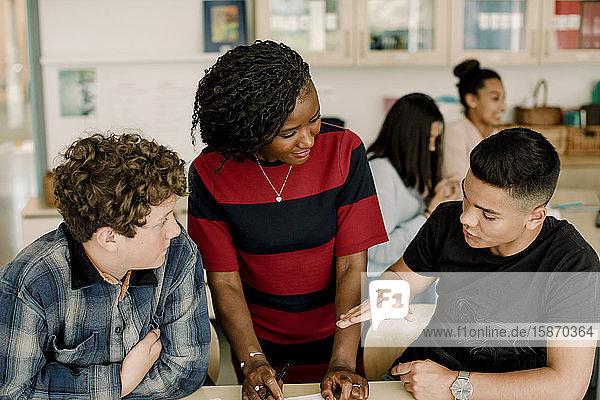 Männlicher Student gestikuliert während einer Diskussion mit einer Lehrerin im Klassenzimmer