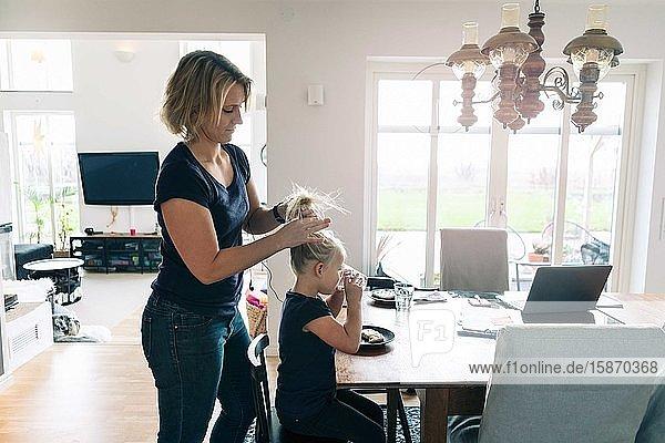 Mutter bindet der Tochter die Haare  während das Mädchen Wasser am Esstisch trinkt