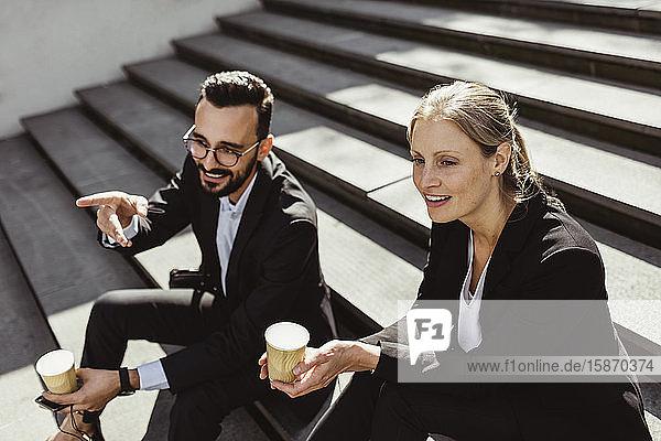 Lächelnder Geschäftsmann zeigt  während er mit einer Mitarbeiterin auf einer Treppe sitzt