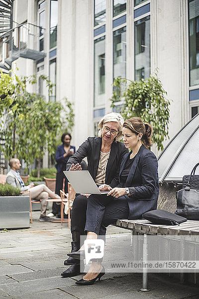 Unternehmerinnen diskutieren über Laptop in voller Länge  während sie auf einer Bank im Bürohof sitzen