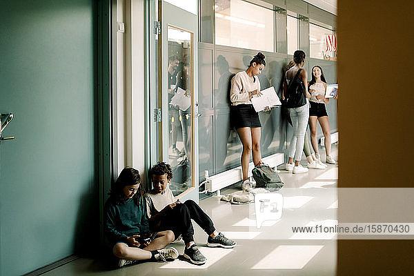 Junge und Mädchen sitzen in der Tür  während sich Schüler der Mittelstufe auf dem Schulkorridor unterhalten