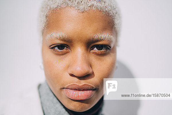 Porträt einer selbstbewussten jungen Frau an der Wand stehend