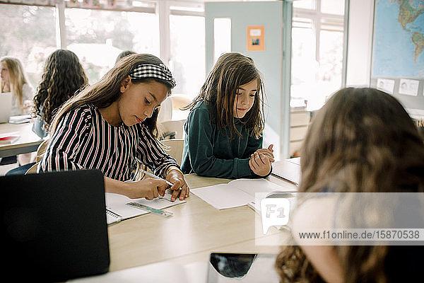Studentinnen lernen am Tisch im Klassenzimmer