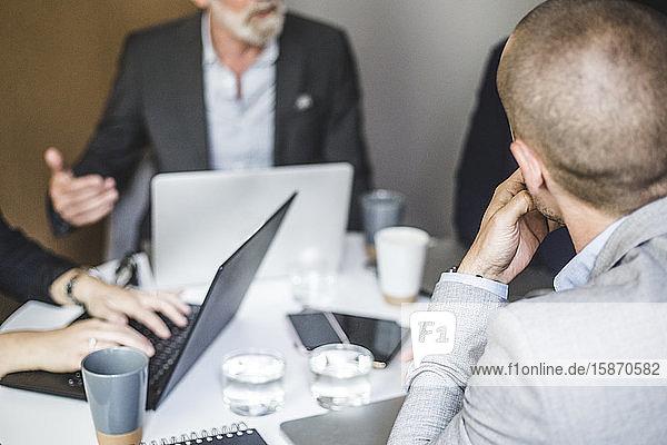 Geschäftsmann diskutiert mit Kollegen  während er während der Sitzung im Sitzungssaal sitzt