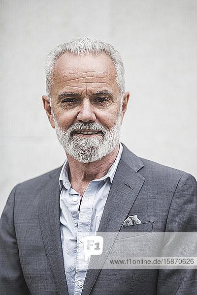 Porträt eines selbstbewussten Senior-Geschäftsmannes an der Wand stehend