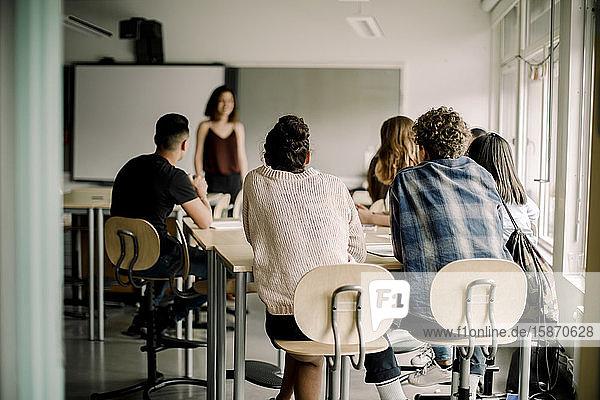 Schüler der Junior High studieren  während eine Lehrerin im Klassenzimmer steht