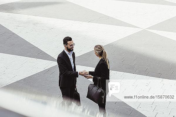 Schrägaufnahme von Geschäftsleuten  die auf der Straße stehen und sich die Hand geben