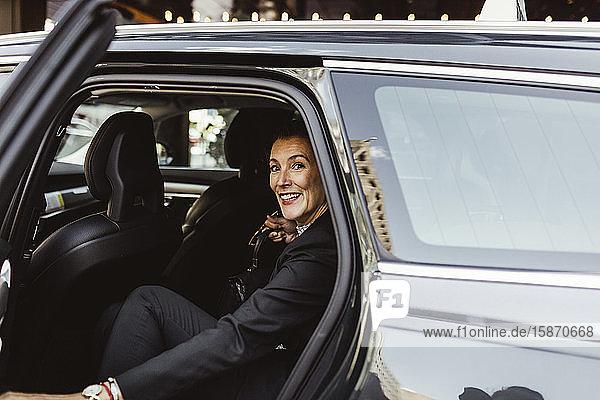 Porträt einer selbstbewussten Unternehmerin  die im Auto sitzt