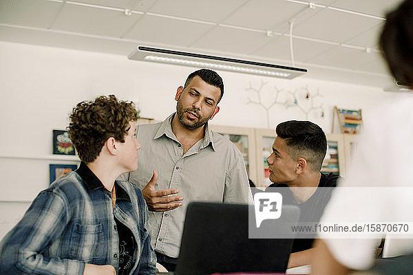 Professor diskutiert mit männlichen Studenten  während er im Klassenzimmer steht