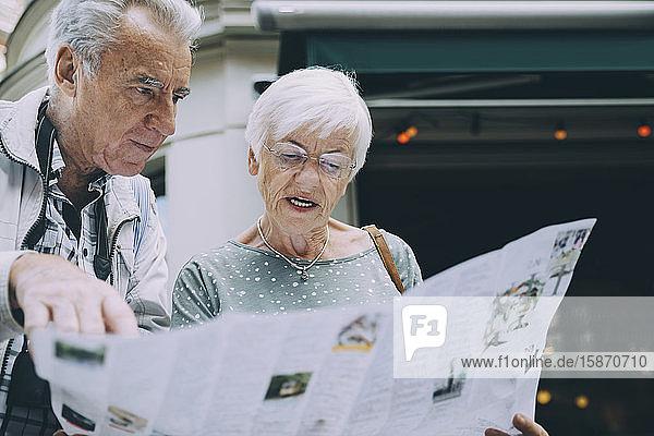 Ältere Frau liest Karte  während sie im Urlaub mit ihrem Partner in der Stadt steht