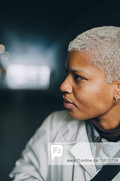 Selbstbewusste junge Frau schaut weg  während sie im Korridor steht