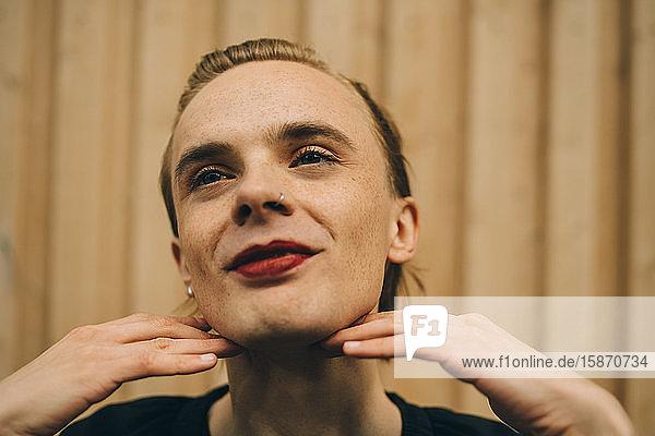 Lächelnder Mann mit rotem Lippenstift steht an Holzwand